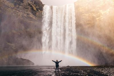 Writing tips. Man showing his hands above in front of a rainbow